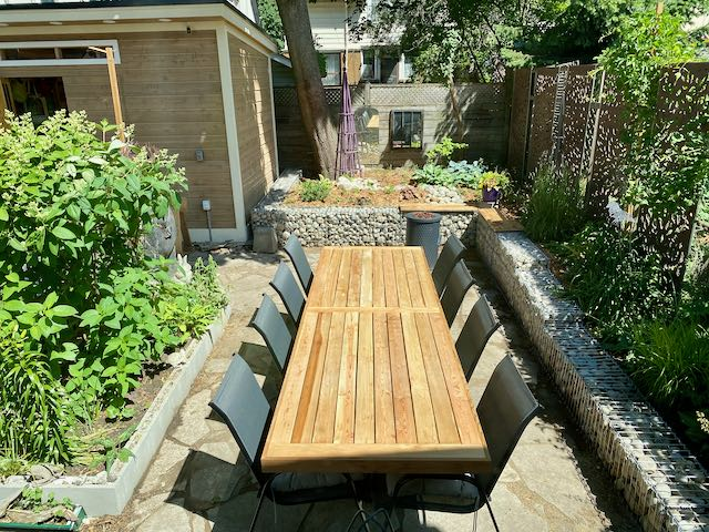 Small urban garden with long dining table and eight chairs surrounded by raised beds