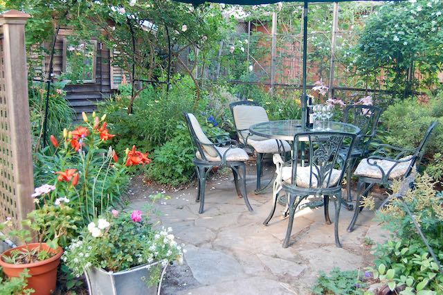 Small patio with round table and crazy paving surrounded by plants