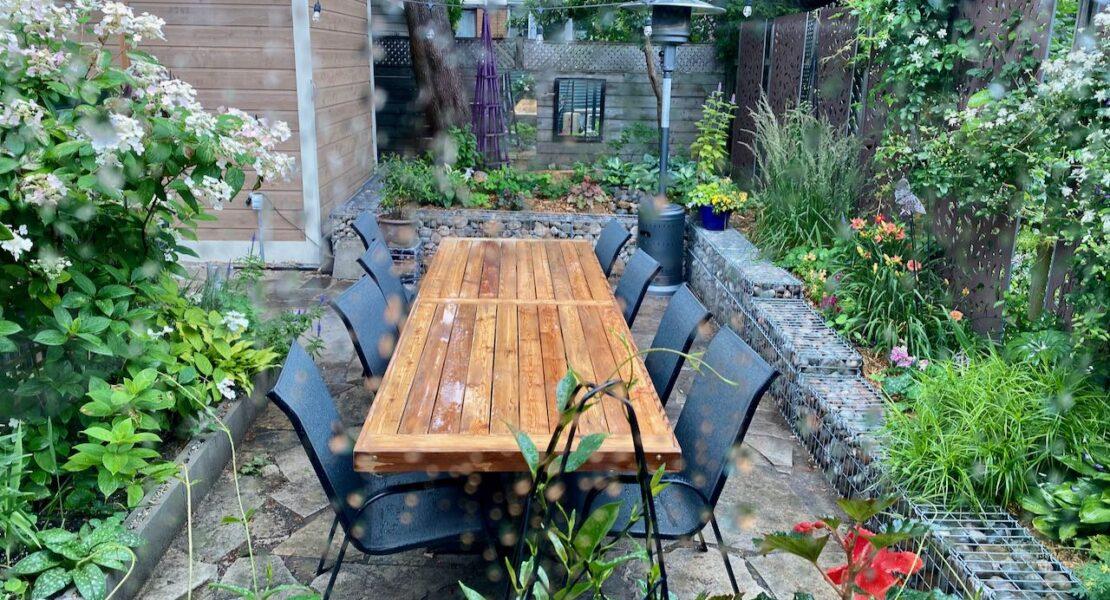 Outdoor dining area defined by gabion cage garden walls